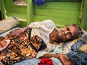 02 JUNE 2015 - KULAI, JOHORE, MALAYSIA: ASMA, 90 years old, a Rohingya refugee from Sittwe, Myanmar, in her home in Kulai. She came to Malaysia on a boat with 50 members of her extended family. They paid traffickers 250,000 Malaysian Ringgits (about $65,000 US) to bring them to Malaysia via traffickers' camps in Thailand. The UN says the Rohingya, a Muslim minority in western Myanmar, are the most persecuted ethnic minority in the world. The government of Myanmar insists the Rohingya are illegal immigrants from Bangladesh and has refused to grant them citizenship. Most of the Rohingya in Myanmar have been confined to Internal Displaced Persons camp in Rakhine state, bordering Bangladesh. Thousands of Rohingya have fled Myanmar and settled in Malaysia. Most fled on small fishing trawlers. There are about 1,500 Rohingya in the town of Kulai, in the Malaysian state of Johore. Only about 500 of them have been granted official refugee status by the UN High Commissioner for Refugees. The rest live under the radar, relying on gifts from their community and taking menial jobs to make ends meet. They face harassment from Malaysian police who, the Rohingya say, extort bribes from them.     PHOTO BY JACK KURTZ
