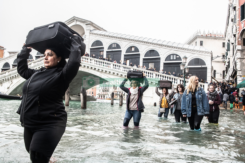 October 29, 2018 - Venice, Italy - People carry luggage over their head. Weather emergency In Venice, italy due to the High water: almost all the city have been underwater with a maximum level reached of 160cm on the sea level. (Credit Image: © Giacomo Cosua/NurPhoto via ZUMA Press)