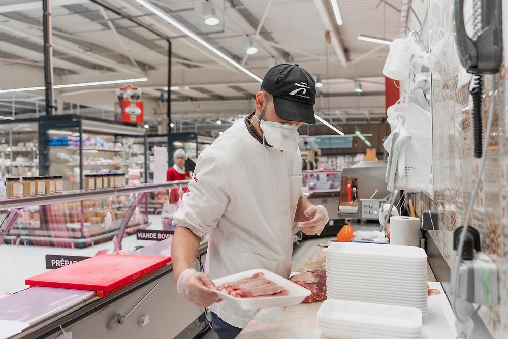 L'Intermarché de La Loupe, le 18 mars 2020.<br /> Chaque employé du supermarché porte un masque et des gants de protection: un boucher prépare des barquettes d'escalopes de porc.
