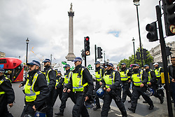 """© Licensed to London News Pictures . 24/06/2017. London, UK. Police on Trafalgar Square keep the two groups separated The English Defence League ( EDL ) hold a March on Parliament , from Charing Cross to Victoria Embankment , opposed by  a counter demonstration by Unite Against Fascism . Scotland Yard said it was using public order laws to restrict the marches """"due to concerns of serious public disorder, and disruption to the community"""" following terrorist attacks in Manchester , Westminster and Finsbury Park and the Grenfell Tower fire  . Photo credit: Joel Goodman/LNP"""