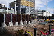 Construction site in Centenary Square and the Library of Birmingham in Birmingham city centre is virtually deserted due to the Coronavirus outbreak on 31st March 2020 in Birmingham, England, United Kingdom. Following government advice most people are staying at home leaving the streets quiet, empty and eerie. Coronavirus or Covid-19 is a new respiratory illness that has not previously been seen in humans. While much or Europe has been placed into lockdown, the UK government has announced more stringent rules as part of their long term strategy, and in particular social distancing.