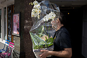 A delivery man carries an orchid through a central London street, on 28th March, 2017, in London, England.