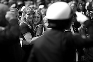 Susie Snyder-Pinchot grieves with her daughter Stephanie Snyder outside the Chrystal Cathedral as police officers salute the body of Buena Park Motor Officer Tyler M. Pinchot following services Thursday September 25, 2003.