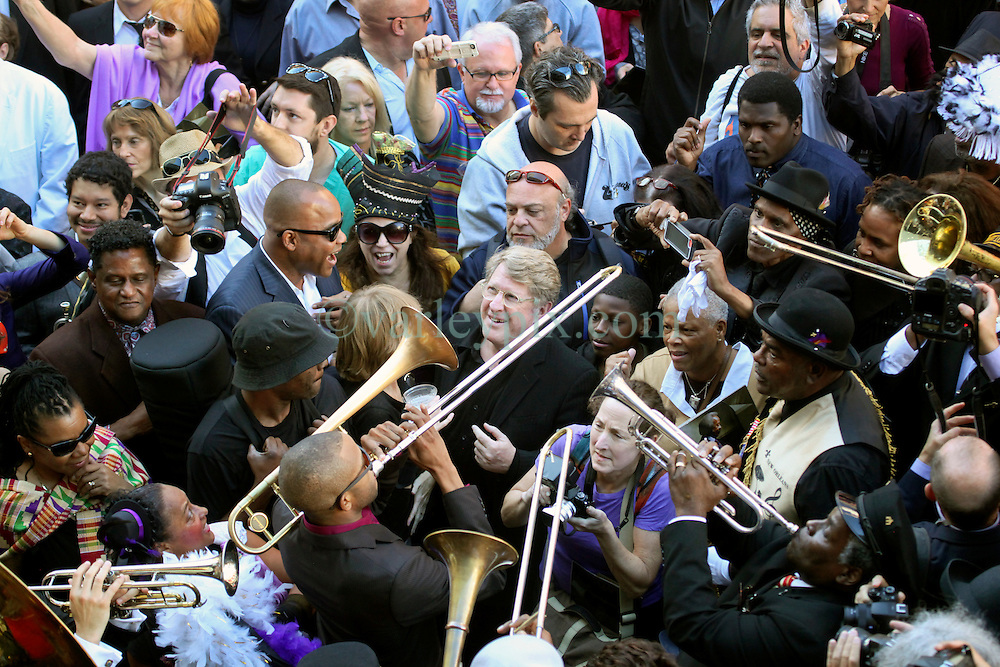 20 November 2015. Orpheum Theater, New Orleans, Louisiana. <br /> Memorial service for musician Allen Toussaint.Troy 'Tombone' Shorty and Quint Davis gather in the street as people  spill out of the Orpheum Theater in a second line procession following the touching memorial service for one of the city's most influential musicians. <br /> Photo; Charlie Varley/varleypix.com