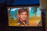 """Merrick, New York, USA. 11th June 2017.  Picture of young boy shown on large screen is """"American Grit"""" TV show contestant CHRIS EDOM, now 48 of Merrick, during Season 2 premiere of the reality show. Edom family and neighbors watched Episode 1 of the Fox network reality TV show on large screen in their backyard. Edom was the last contestants picked for a team."""
