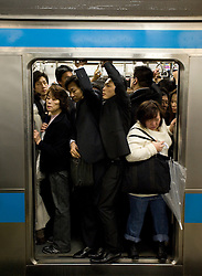 Overcrowded commuter train at station in Tokyo during rush hour