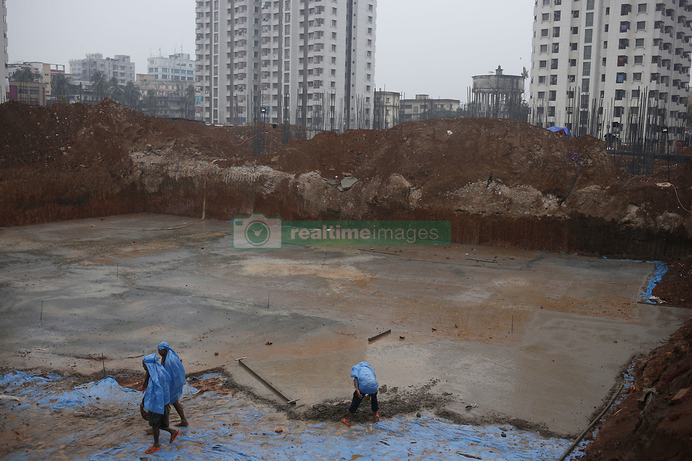 """December 17, 2018 - Dhaka, Bangladesh - Construction workers use plastic sheets to during rain as they are working a construction site in Azim Pur. According to news, part of the country experienced light to moderate rain due to the cyclonic storm, """"Phethaiâ (Credit Image: © MD Mehedi Hasan/ZUMA Wire)"""