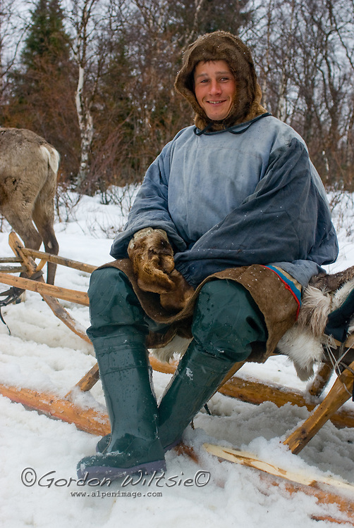 North of the Arctic Circle in Russia, Arthum Khantazeski, a nomadic Komi reindeer herder, relaxes on his sled after a long day watching the animals owned by his clan.