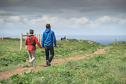 Tourists stroll along the footpaths on the cliffs at Carnewas at Bedruthan in Cornwall.