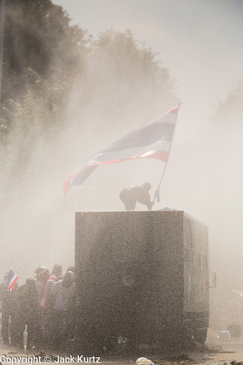 02 DECEMBER 2013 - BANGKOK, THAILAND: An anti-government protestor flies a Thai flag in a cloud of chemical dispersal agents and tear gas fired from water cannons during anti-government riots in Bangkok. Anti-government protestors and Thai police continued to face off Monday for a second day. Police used tear gas, water cannons and rubber bullets against protestors who charged their positions near the barriers on Chamai Maruchet bridge on Phitsanulok Road, which leads to the Government House.     PHOTO BY JACK KURTZ