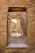 Walk through ancient doorways to mysterious rooms in Pueblo Bonito, a monumental public building (Puebloan Great House) occupied from around 828 to 1126 AD, now preserved at Chaco Culture National Historical Park, New Mexico, USA. The huge D-shaped complex of Pueblo Bonito enclosed two plazas with dozens of ceremonial kivas, plus 600 rooms towering 4 and 5 stories above the valley floor. The functions of this building included ceremony, administration, trading, storage, hospitality, communications, astronomy, and burial, but few living quarters. Chaco Culture NHP hosts the densest and most exceptional concentration of pueblos in the American Southwest and is a UNESCO World Heritage Site, located in remote northwestern New Mexico, between Albuquerque and Farmington. From 850 AD to 1250 AD, Chaco Canyon advanced then declined as a major center of culture for the Ancient Pueblo Peoples. Chacoans quarried sandstone blocks and hauled timber from great distances, assembling fifteen major complexes that remained the largest buildings in North America until the 1800s. Climate change may have led to its abandonment, beginning with a 50-year drought starting in 1130.