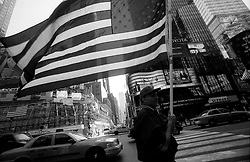 14 Sept 01. Times Square, New York City, NY.<br /> Flying the flag. A patriotic citizen walks through Times Square following the heinous terrorist attacks on the World Trade Center Twin Towers. <br /> Photo credit©; Charlie Varley/varleypix.com.