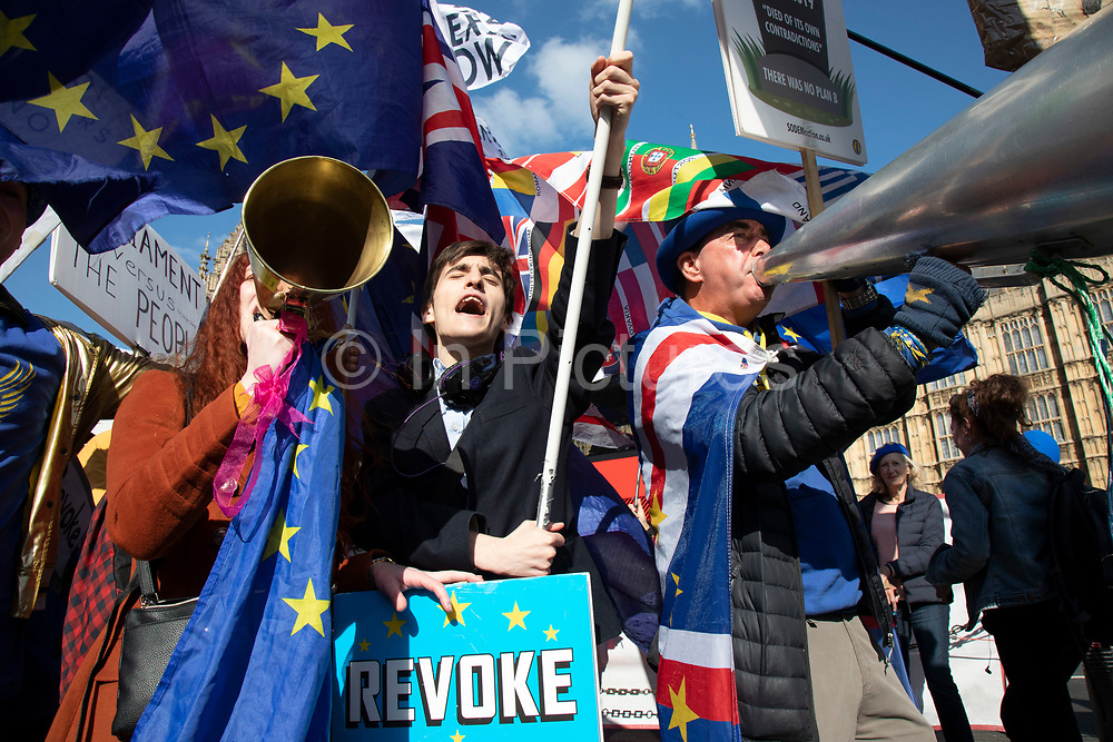 Young anti Brexit protesters Shaun Smith-Milne, from Liverpool and Florine Pochet from Lille in France shout anti-Brexit slogans and wave flags with other protesters opposite Parliament in Westminster as the Prime Minister arrives in Brussels to request an extension to Article 50 so the UK can continue to try to agree a Brexit Withdrawal Agreement on 10th April 2019 in London, England, United Kingdom. With just two days until the UK is supposed to be leaving the European Union, the delay decision awaits.