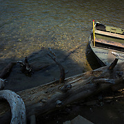 An old fishing boat is tied to a fallen tree at Lake Mary in Mammoth Lakes, CA