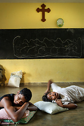 Residents of the Teevanandam family, including Jennifer, 13, at right, who lost her mother, wake up inside a classroom at St. Cecilia's Convent, Batticaloa, Sri Lanka, Jan. 29, 2005. Residents of the small Christian village Dutch Bar spent more than six weeks in a makeshift refugee camp at the local convent recovering from the devastating tsunami that hit the eastern and southern borders of Sri Lanka. They were then moved into another temporary living camp, while awaiting the building of new homes. More than 150 members in this community of less than 1000 people died in the tragic event.