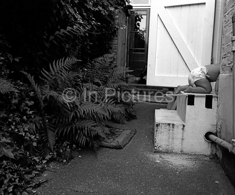 """""""On all fours."""" An eleven month-old infant crawls up some back garden steps and into her parents' house. Her head and shoulders are already hidden as she disappears inside. She is exploring a familiar world, being bold, gaining strength and confidence to move independently to eventually stand upright and walk unaided. Someone has taped a short stick to the upper step to help her position herself downwards when exiting the house backwards.  Wearing only a nappy (diaper) it is clearly a warm summer's day. This is from a documentary series of pictures about the first year of the photographer's first child Ella. Accompanied by personal reflections and references from various nursery rhymes, this work describes his wife Lynda's journey from expectant to actual motherhood and for Ella - from new-born to one year-old."""