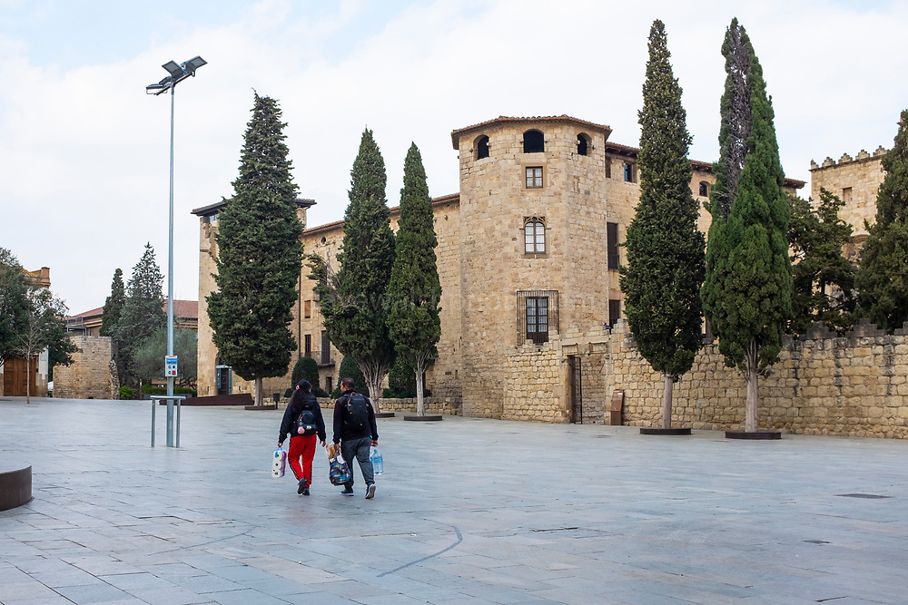 A couple carry shopping through the normally bustling streets in Sant Cugat del Valles, a city of some 90,000 people outside Barcelona, on the day before Spain exerted a state of Emergency to deal with the spread Coronavirus. Spain is one of the worst affected countries. Schools and retail businesses are closed, except for supermarkets and pharmacies.