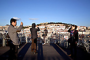 Tourists taking pictures facing Castelo de S. Jorge hill , from the walkway at the top of Elevador de Sta. Justa. This lift, built in 1902 with 45 metres tall, links the higher districts with Baixa in the hill directly opposite to the castle, in central Lisbon.