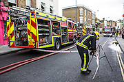 A London Fire Brigade firefighter seals off an emergency area with barricade tape to ensure public safety on a street in North London, United Kingdom.  Four fire engine trucks have responded to emergency caused by an explosion in a small shop.