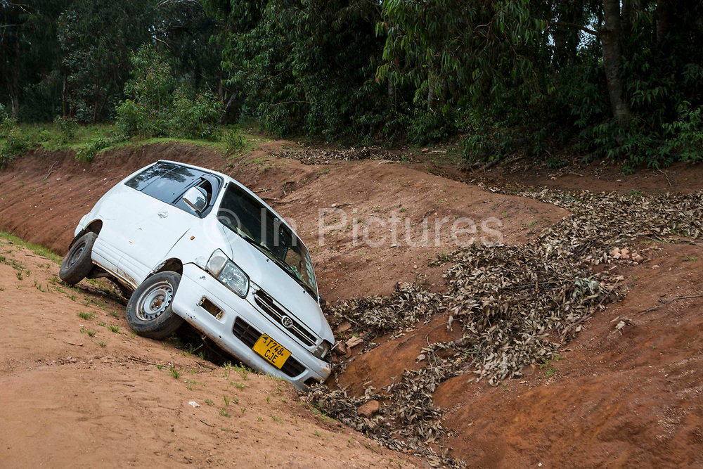 A white Toyota people carrier lays in a ditch after an accident on the side of a dirt road in Manyara district, Tanzania, East Africa.