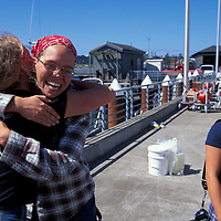 USA, Oregon, Friends embrace after voyage on U of Washington research ship R/V Thomas G. Thompson