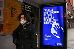 © Licensed to London News Pictures. 07/01/2021. London, UK. A commuter wearing a protective face covering stands next to Transport for London's 'We clean our transport network regularly with antiviral disinfectant' campaign poster at a bus stop in north London.  Photo credit: Dinendra Haria/LNP