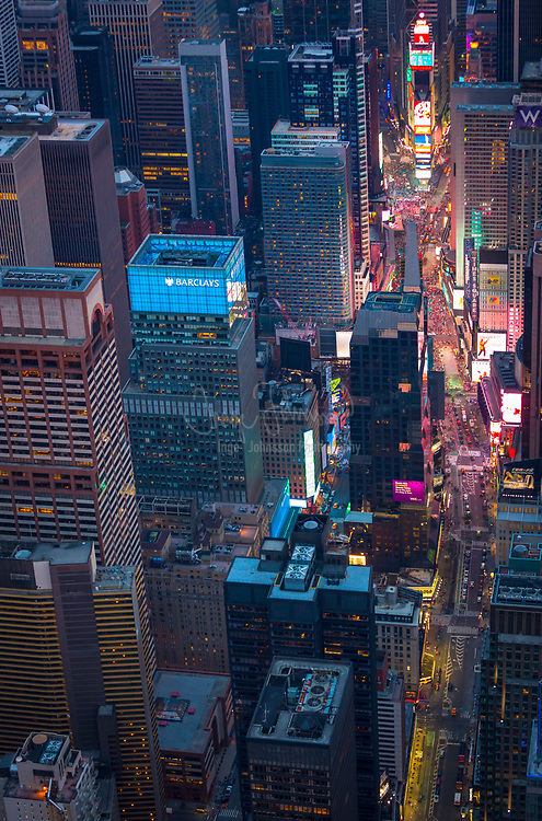 "Aerial photograph (helicopter). Times Square is a major commercial intersection and neighborhood in Midtown Manhattan, New York City, at the junction of Broadway and Seventh Avenue, and stretching from West 42nd to West 47th Streets. Brightly adorned with billboards and advertisements, Times Square is sometimes referred to as The Crossroads of the World, The Center of the Universe, the heart of The Great White Way, and the ""heart of the world"". One of the world's busiest pedestrian intersections, it is also the hub of the Broadway Theater District and a major center of the world's entertainment industry. Times Square is one of the world's most visited tourist attractions, drawing an estimated 50 million visitors annually. Approximately 330,000 people pass through Times Square daily, many of them tourists, while over 460,000 pedestrians walk through Times Square on its busiest days."