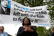 East End, London July 5th 2014. Rally and march against proposed cuts to National Health Service doctors' surgeries , specifically MPIG (Minimum Practice Income Guarantee payments) brought in to ensure practices in deprived areas had enough money to deliver high quality General Practice services. Dianne Abbott, Labour MP for Hackney North and Stoke Newington makes a speech beneath a banner with a quote from Nye Bevan, credited with setting up the NHS in 1948.