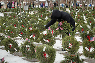 Goshen, New York - A girl places an American flag on a wreath during a Wreaths Across America ceremony at Orange County Veterans Memorial Cemetery on Dec. 16, 2017. About 3,000 wreaths were placed at graves, and small American flags were added to the wreaths at veterans' graves.