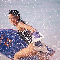 Kanoe running in shore break with body board and fins at Sandy Beach on eastern coastline of Oahu, Hawaii