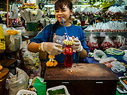 27 FEBRUARY 2019 - BANGKOK, THAILAND: A woman in Pak Klong Talat, Bangkok's flower market, prepares an offering of Red Fanta and flower garlands in the market. Bangkok, a city of about 14 million, is famous for its raucous nightlife. But Bangkok's real nightlife is seen in its markets and street stalls, many of which are open through the night.        PHOTO BY JACK KURTZ