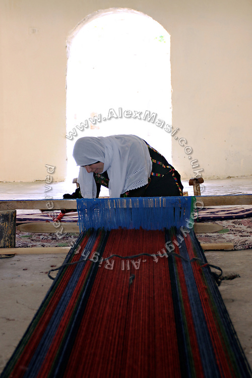 Sabha, 49-year-old Bedouin woman, performing traditional weaving for a local organisation selling traditional work made by Bedouin women in the recognised town of Lakyia. Her mother and grandmother did the same, but her two daughters have jobs as teachers in Israeli schools and have refused to learn. The legacy of traditional weaving in her family will stop with Sabha. She makes 15-20 meters of fabric a month in her spare time, earning around 130 NIS (approx. US 20$) per metre. Lakyia Weaving Project has been thought as a way to emancipate women from their husband and empower local women that would have no money for them, or would have their finances in total control of their husband.