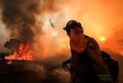 A firefighter watches as a helicopter making a drop on a wildfire near Placenta Caynon Road in Santa Clarita, Calif., Sunday, July 24, 2016.(AP Photo/Ringo H.W. Chiu)