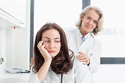 Female doctor consoling collegue