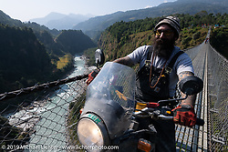 Spoke and Dagger's Chris Drew riding a Royal Enfield Himalayan on the Kushma - Gyadi suspension bridge over the Modi River (the highest, at 384 feet, and longest, at 1,128 feet, suspension bridge in Nepal) during Motorcycle Sherpa's Ride to the Heavens motorcycle adventure in the Himalayas of Nepal. On the sixth day of riding, we went from Tatopani to Pokhara. Saturday, November 9, 2019. Photography ©2019 Michael Lichter.