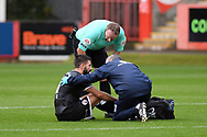 Crawley Town midfielder George Francomb (4) receives treatment before being substituted during the EFL Sky Bet League 2 match between Cheltenham Town and Crawley Town at Jonny Rocks Stadium, Cheltenham, England on 10 October 2020.