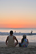 Before sunrise, early morning on a part of China beach in Danang. A man and his daughter are seated in front of the beach, waiting for the sun to rise. We only see their back. In the water, some people are swimming.