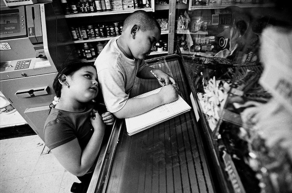 A Guatamalean brother and sister do their homework on top of a freezer in their family's West Philadelphian convenience store.