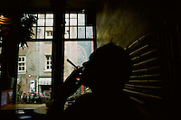 A silhouetted man inhaling a joint in an Amsterdam coffeeshop where marijuana is sold and smoking permitted.