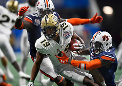 UCF Knights kick returner Mike Hughes (19) is tackled by Auburn defenders during the second half of the Chick-fil-A Peach Bowl NCAA college football game at the Mercedes-Benz Stadium in Atlanta, January 1, 2018. UCF won 34-27 to go undefeated for the season. (David Tulis via Abell Images for Chick-fil-A Peach Bowl)