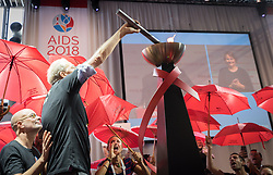 """26 July 2018, Amsterdam, the Netherlands: Demonstrators shout """"shame, shame, shame"""" as the Positive Flame, described as a """"torch of inclusion"""" is lit at the 2018 International AIDS Conference. The torch is to connect the 2018 conference with the 2020 conference, which is expected to take place in the United States, and the protestors, many of whom are sex workers or are part of other key populations, object because people from key populations as well as other groups, such as Muslims, may have difficilties getting a visa to travel to the United States. """"No conference in the United States, no conference in the United States,"""" they continued to chant. The Positive Flame is intended to travel from one International AIDS Conference to the next, and echoes the Olympic Flame that was introduced at the Olympic Games in Amsterdam in 1928."""