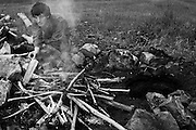 Charlie, a 16-year-old member of the Idaho Light Foot Militia from Couer d'Alene, Idaho, stokes the fire during a break in the action at a weekend-long training exercise near Priest Lake, Idaho.