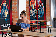A woman in a blue dress working on a laptop outside the Ritzy Picturehouse cinema as temperatures reach low 30s across the capital on the 24th July 2019 in South London in the United Kingdom.