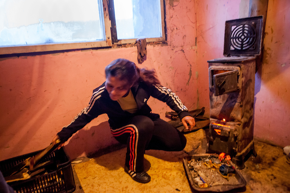 """Milena (mother of four daughters and a son) heating with wood. The family moved into another and final compensatory flat at Lunik IX after their first building (""""Hrebenova 34-36"""") was demolished by the city of Kosice in August 2014, the second flat was not in a appropriate condition."""