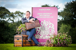 © Licensed to London News Pictures. 14/09/2017. Harrogate UK. Show Director Nick Smith sits on the Yorkshire Flower show's exhibition, Postcards from the Hedge on staging day at the Autumn Flower show. The exhibition is designed to highlight that every year thousands of plant cuttings, seed & bulbs find their way back to the UK in suitcases from around the world, but garden enthusiasts could get more than they bargain for if their prized new specimen turns out to be a plant thug. The Autumn Harrogate Flower show starts tomorrow at the Great Yorkshire show ground. Photo credit: Andrew McCaren/LNP
