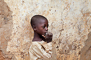 A boy sucking his finger covered in dust, is wandering around Bagega, pop. 9000, a large village affected by lead poisoning due to the unsafe techniques employed for extracting gold, in Zamfara State, Nigeria. It is mainly caused by ingestion and breathing of lead particles released in the steps to isolate the gold from other metals. This type of lead is soluble in stomach acid and children under-5 are most affected, as they tend to ingest more through their hands by touching the ground, and are developing symptoms often leading to death or serious disabilities.