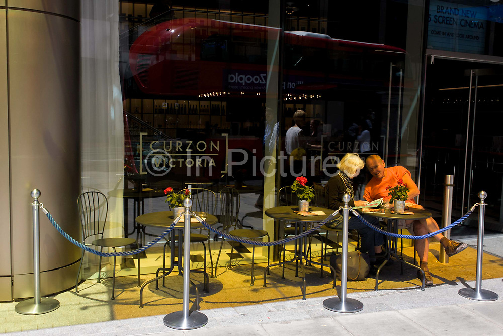 Orange-clothed man sits at cafe table, under orange glass in bright sunshine in central London. Under a coloured-glass roof above, two people sit at a table of the new Curzon (Victoria) cinema in Westminster, central London. The man wears a bright orange shirt which is exaggerated by this overhead glass, his skin also given a false hue while along the other tables, more orange and yellow light shines on to their surfaces.
