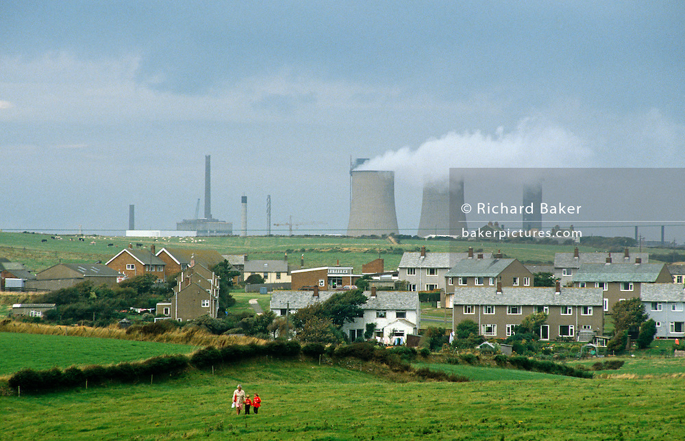 Making their way across a field, alongside a hedge, and away from a collection homes a mother and her two children walk from the direction of massive chimneys and cooling towers. The instillation in the distance is the Sellafield. Formerly known as Windscale, Sellafield (operated by Sellafield Ltd) is a nuclear processing and former electricity generating site, close to the village of Seascale on the coast of the Irish Sea in Cumbria, England. The site has been the subject of much controversy because of discharges of radioactive material into the sea, mainly accidental but some alleged to have been deliberate. 1983 was the year of the 'Beach Discharge Incident' in which high radioactive discharges containing ruthenium and rhodium 106, both beta-emitting isotopes, resulted in the closure of a beach. BNFL received a fine of £10,000 for this discharge.