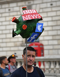 © Licensed to London News Pictures. 26/06/2021. London, UK.  A protester wields a corona virus shaped placard with media news outlets. Anti-vaccination and anti-lockdown demonstrators converge on Downing Street after a day of protest in Central London.  Photo credit: Guilhem Baker/LNP