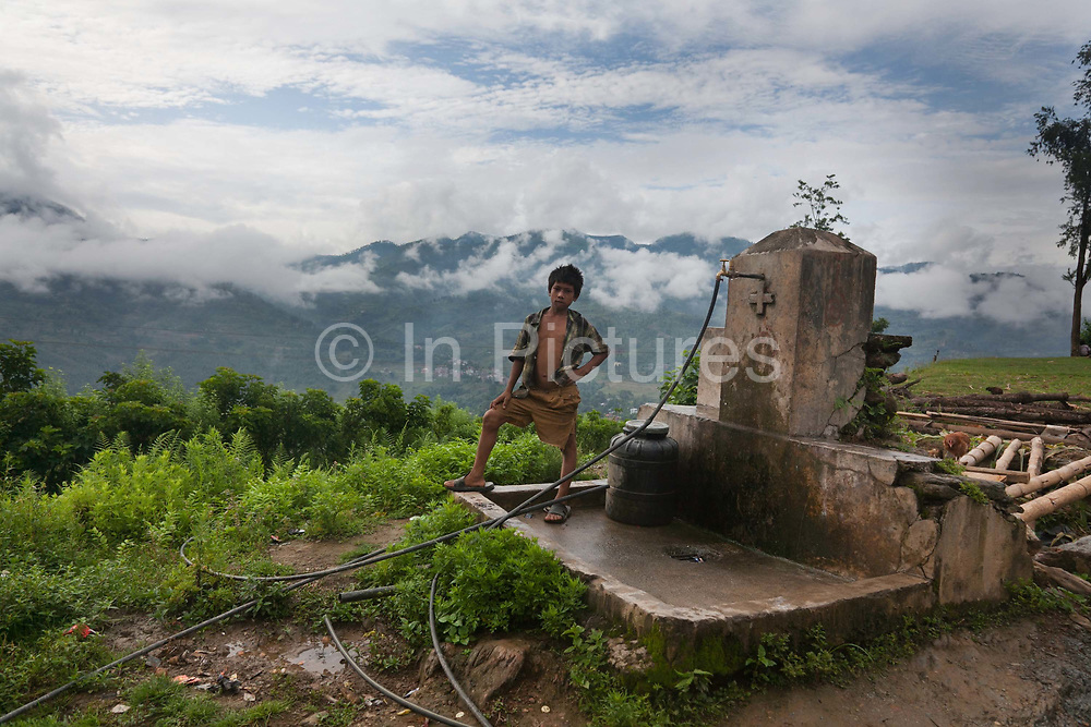 A public water tap above Dhading, next to Pasupati School. School is out for the summer and most children give a hand at home during the break. Very few homes have running water and water is collected from centralised public taps with water from springs higher up in the mountains.